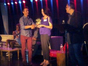 Producer Larry Laboe presenting an award to  Jeanette Brill of Blumhouse Productions.