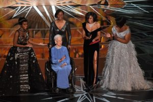 NASA physicist Katherine Johnson is surrounded by actresses Janelle Monae, Taraji P. Henson and Octavia Spencer as they present on stage the Documentary (Feature) award at the 89th Academy Awards.