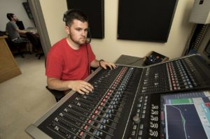 Ryan Tribou, a senior student in the NESCom Live Sound Technology program, operates the new Calrec Audio Brio. In the background, operating the video switcher, is Edward Goguen, assistant professor, academic director, and audio programs coordinator at NESCom.
