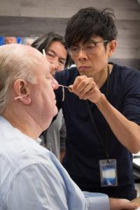 Kazu Hiro putting prosthetics on John Lithgow
